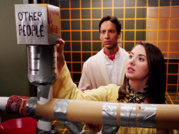 dans une pièces couverte d'une grille orange, une jeune femme tripote une machine en carton au grand désespoir du génie asocial derrière elle
